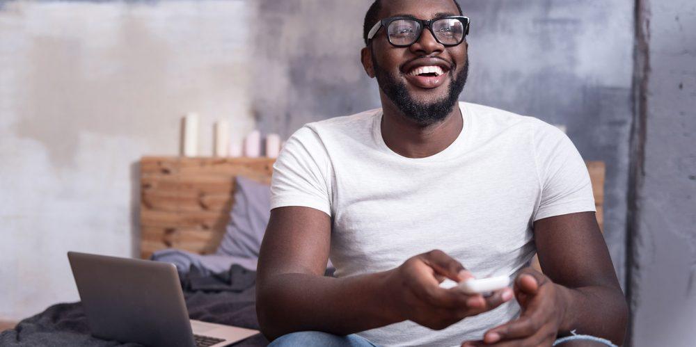 homem de óculos assiste tv